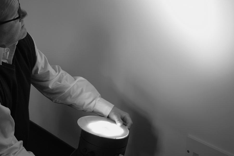 Mann betrachtet Lichtreflexionen an einer Wand